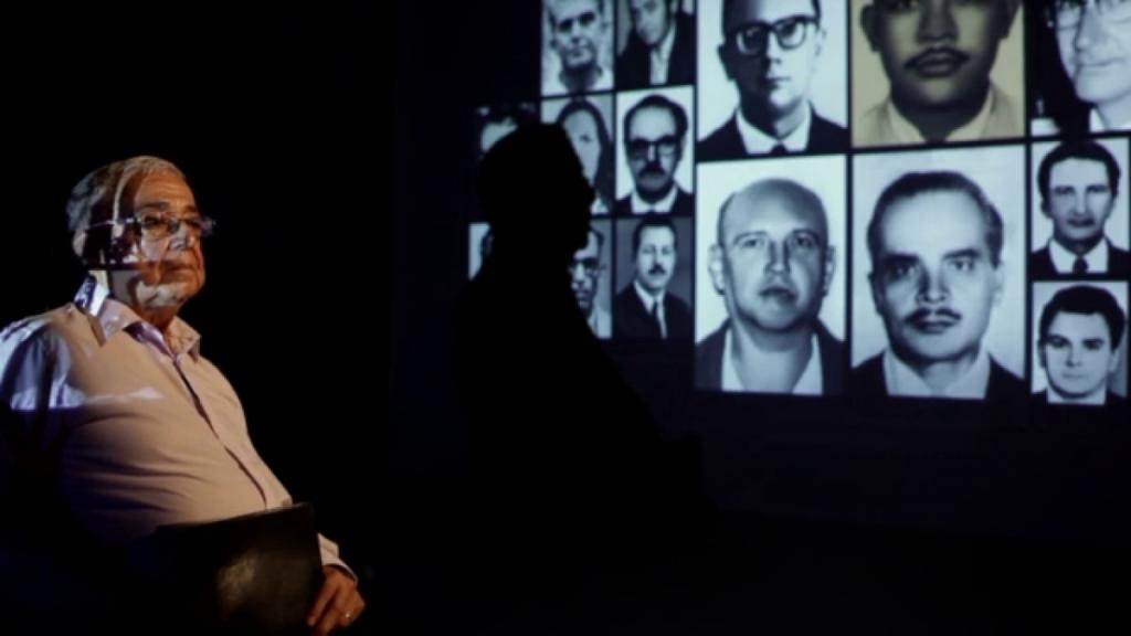 Pastor Cláudio sentado. Ao fundo, imagens de vítimas da ditadura.
