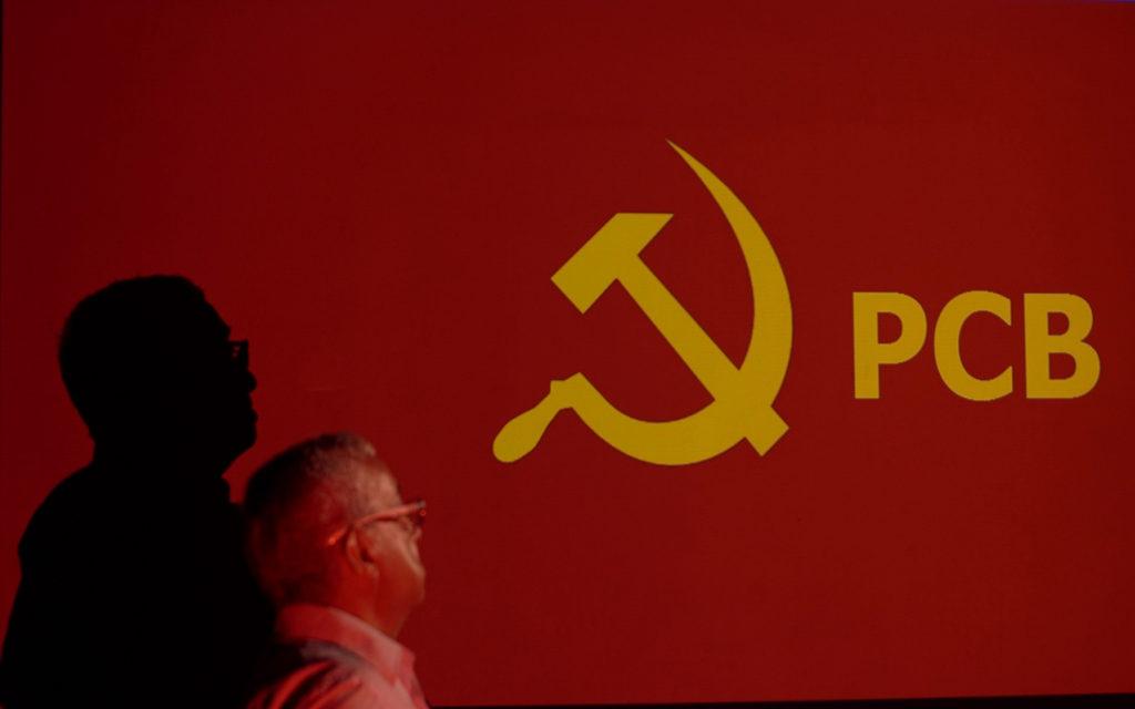 Pastor Cláudio observa imagem do partido comunista brasileiro